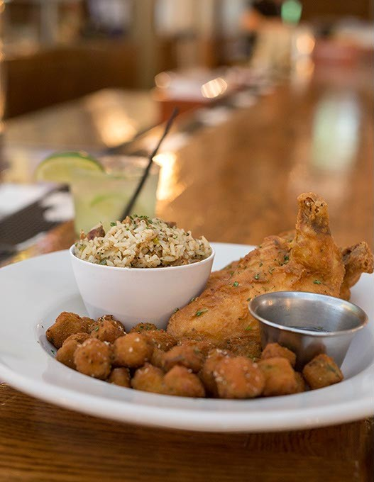 JAX Soul Kitchen serves Smoked Fried Chicken with Dirty Rice, Fried Okra and a Basil Brazilian cocktail on Monday, June 27, 2016 in Norman, Oklahoma. - EMMY VERDIN
