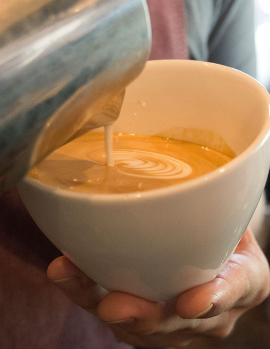A barista creates latte art at Elemental Coffee, Monday, May 15, 2017. - CARA JOHNSON