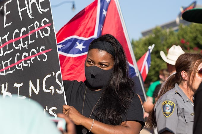 Black Lives Matter protestor, Nicole Barker, holds a sign in front of a group of Confederate flag carrying protestors on Sunday, July 10, 2016 in Oklahoma City. - EMMY VERDIN