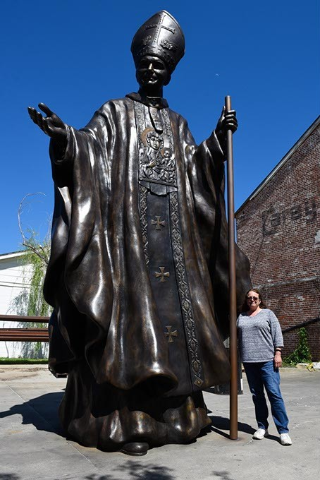 Teresa Clark poses for a photo with a 20-foot-tall monument to Pope John Paul II that she designed, at The Crucible Foundry in Norman, Thursday, May 12, 2016. - GARETT FISBECK