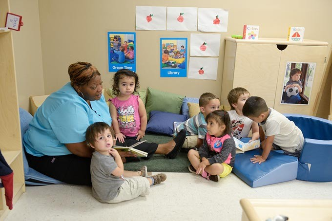 Danyale Murray reads to children at Kidzone Learning Center, an OKC childcare facility benefiting from a partnership with Sunbeam Family Services.   Photo Garrett Fisbeck