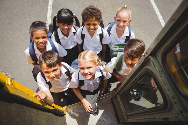 Cute schoolchildren getting on school bus outside the elementary school - BIGSTOCK
