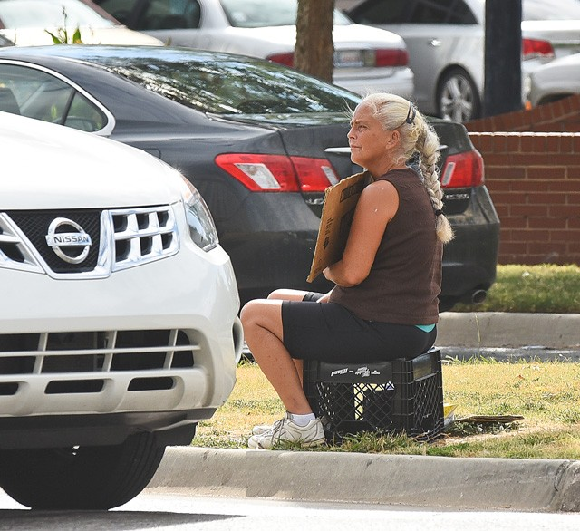 A woman begs for money from one of Oklahoma City's medians in 2015. (Photo Gazette/file)
