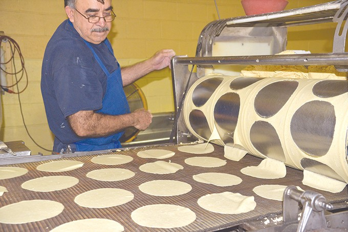 Jorge Flores oversees corn tortillas that will be fried for chips and taco shells. - JACOB THREADGILL