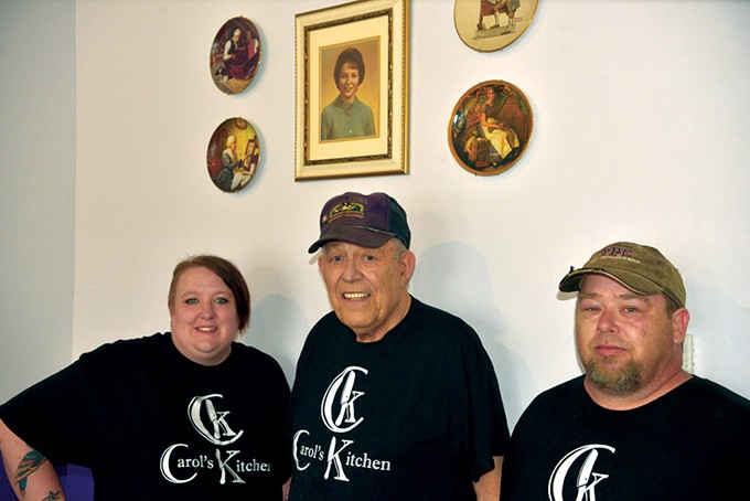 Hailey, Jim and Brian Kahoe stand underneath a photo of Carol Kahoe at Carol's Kitchen in Norman. - | PHOTO JACOB THREADGILL