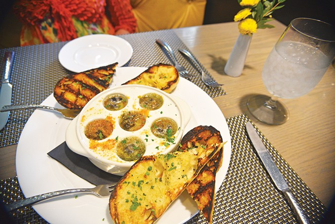 Escargot is served in garlic and parsley butter with grilled bread. - JACOB THREADGILL