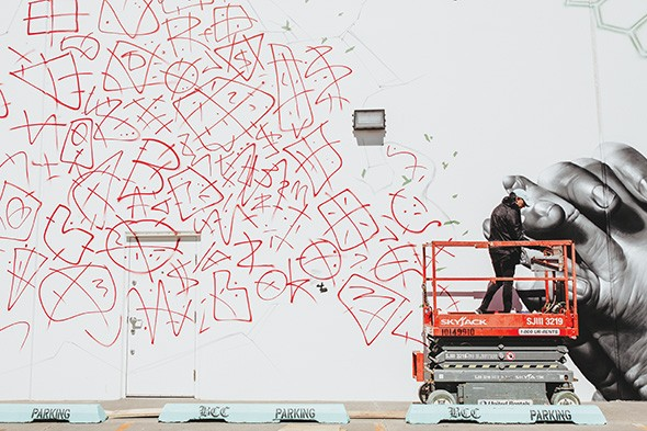 Street artist Jeks lays down the foundation for his second mural on the southern wall of BCC Collective. - ALEXA ACE