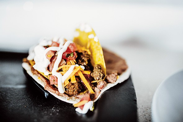 The taco dog is a hot dog topped with ground beef, cheese, pico de gallo and sour cream in a - crispy corn tortilla shell layered with refried beans and wrapped in a flour tortilla. - ALEXA ACE