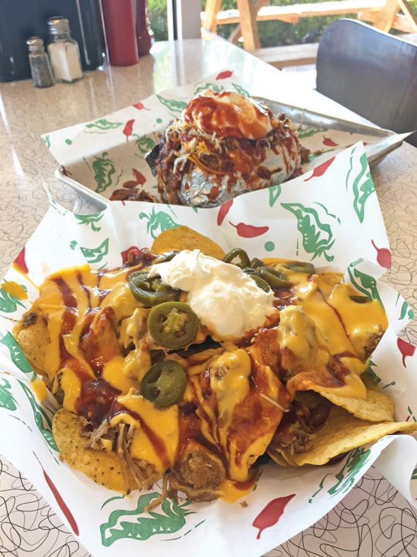 Big O baked potato with pulled pork, baked beans, cheese and sour cream and a half order of barbecue nachos - JACOB THREADGILL