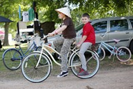 Jazlyn Hancock, 11, and Emory Strader, 9, ride on a bike during the Queen of the Prairie festival in Guthrie, Friday, May 1, 2015. - GARETT FISBECK