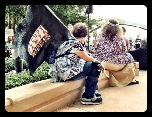 A member of Occupy Tampa sits outside Orlando City Hall at the People's Convention of Florida. Photo by Rob Bartlett.
