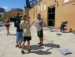 A news reporter interviews people working out at a nearby gym about the downtown explosion. Photo by Dave Plotkin.