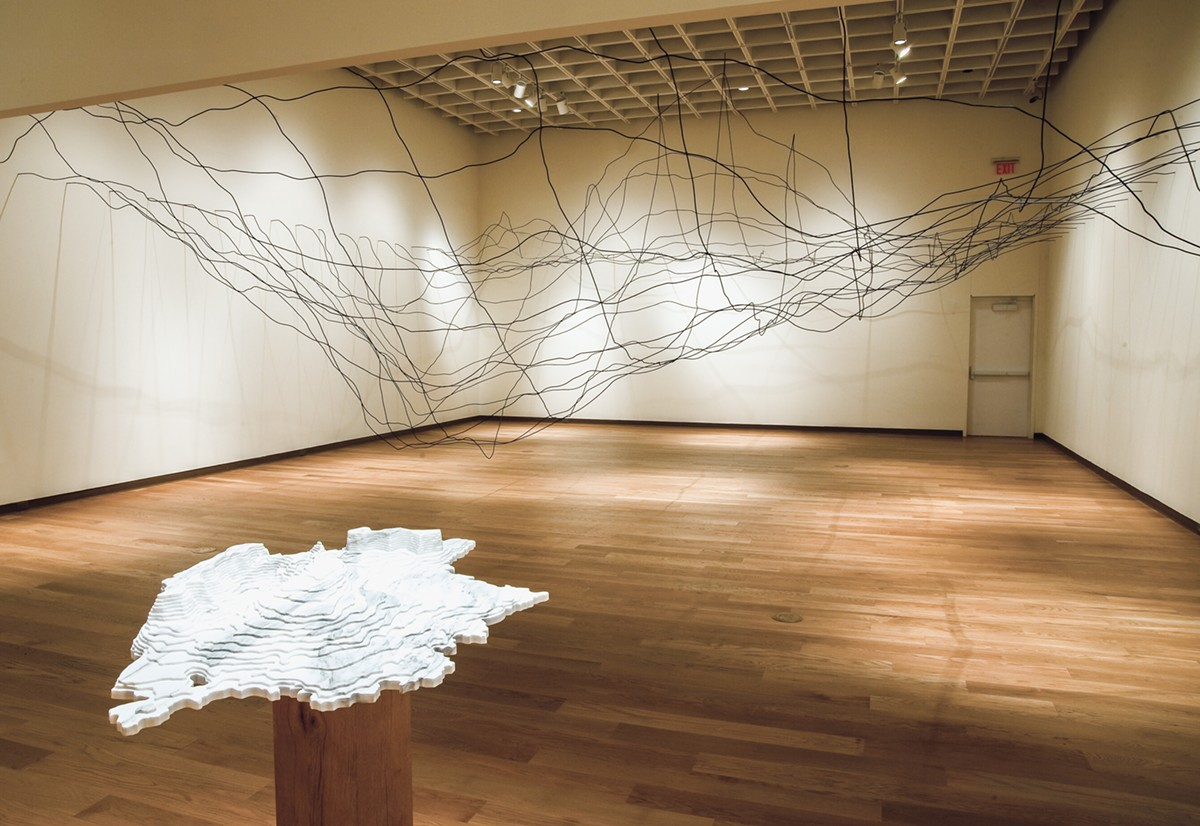 Installation view of the exhibition: Maya Lin: A History of Water, Orlando Museum of Art, January 31–May 10, 2015. Foreground in marble: Disappearing Bodies of Water: Aral Sea, 2013. Background: Water Line, 2006, © Maya Lin Studio, courtesy Pace Gallery.