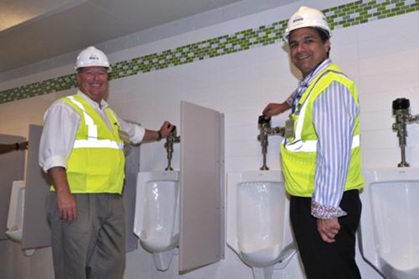 Orlando Mayor Buddy Dyer (left) and Orlando Magic President Alex Martins (right) get ready to flush your money down the drain