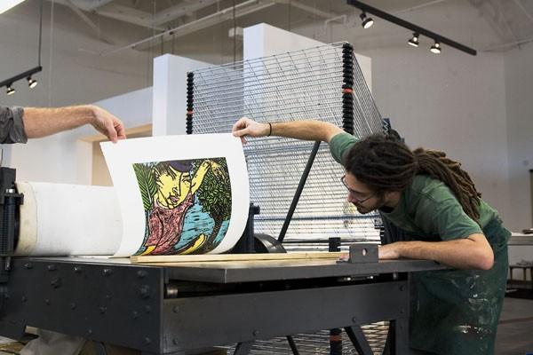 "Print on Demand: Jon Didier, an intern at Flying Horse Editions, examines Yuji Hiratsuka's ""Bewitching Ritual"" woodcut print as it comes off the press - DANIEL DORSA"