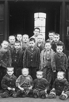 A group of children pose outside a 19th century group home