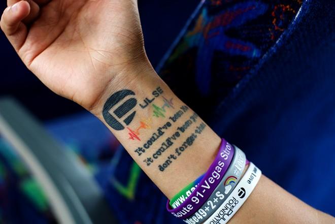 Enakai Mpire shows his tattoo dedicated to Pulse. - PHOTO BY MONIVETTE CORDEIRO