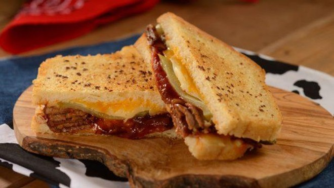 BBQ Brisket Melt, a Texas-style smoked brisket features cheddar, Monterey Jack, pickles, and BBQ sauce on garlic butter-grilled sourdough. - PHOTO VIA DISNEY