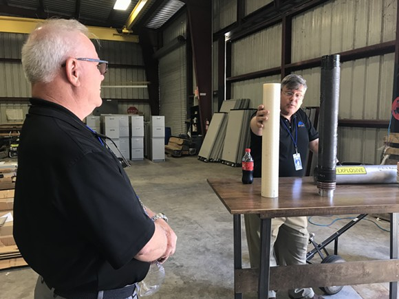 VP of Propulsion Robert Fabian (right) and Chief Technologist Ron Jones (left) present two cylinders of 3D-printed rocket fuel during a media tour on Monday, May 7 at Rocket Crafters' Cocoa Beach manufacturing facility. - PHOTO BY JOEY ROULETTE