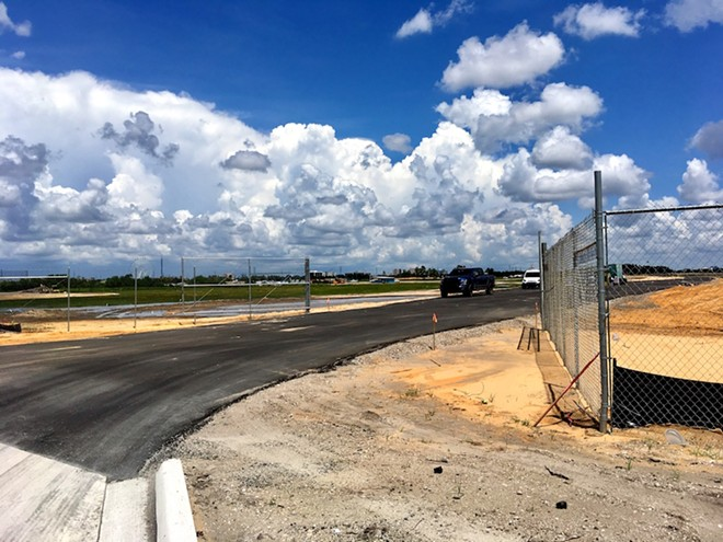 The new paved road is believed to provide access for grading and eventually construction on the expansion land. The entrance is off Destination Parkway near UCF's Rosen College of Hospitality. - PHOTO BY PAUL BRINKMANN