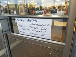 "A handwritten sign on the front door of Belk explaining the store is closed ""due to Mother Nature."" Workers are seen just inside with giant dryers working to clean up a recent leak."