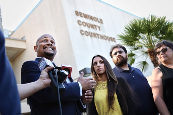 Carlos Leach, far left, and his client Minaz Mukhi-Skees, second-left, speak at a press conference at the Seminole County Courthouse. - PHOTO BY JOEY ROULETTE