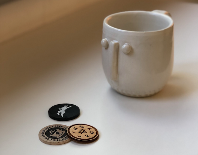 Coffee tokens from Lineage, Easy Luck and Ace Cafe, with a cup by Koozeh Pottery - PHOTO BY JESSICA BRYCE YOUNG