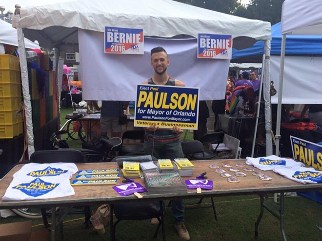 A picture of the Paulson for Mayor table at Orlando Pride shows T-shirts and bumper stickers bearing a fountain illustration. - PHOTO VIA PAULSON FOR MAYOR ON FACEBOOK