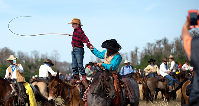 """Justin Mickelsen, 13, stands atop his horse and cracks his whip. """"Awesome,"""" said Mickelsen of Mobile, Alabama, about his six-day trip into the Florida wilderness."""