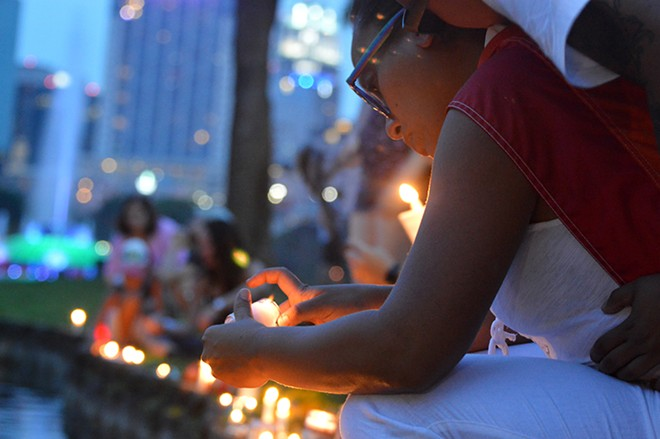Lighting a candle at Lake Eola. - PHOTO BY MONIVETTE CORDEIRO