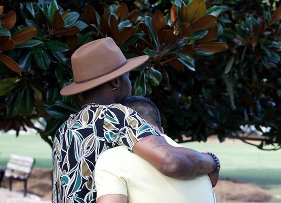 Demetrice Naulings comforts Eddie Justice's boyfriend, Alejandro Ortega. - PHOTO BY MONIVETTE CORDEIRO