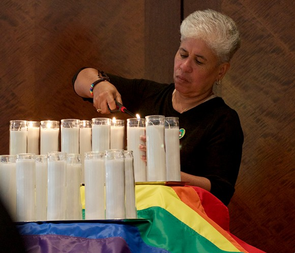 Nancy Rosado of Somos Orlando lights 49 candles in honor of the Pulse victims. - PHOTO BY MONIVETTE CORDEIRO