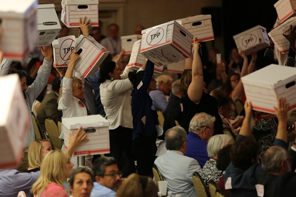 Democratic delegates raise cardboard boxes meant to represent hundreds of thousands of signatures against the Trans-Pacific Partnership. - PHOTO BY JOEY ROULETTE