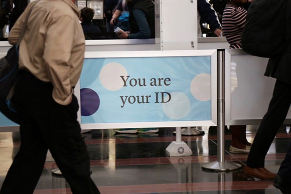 """A railing with a facial recognition company's branding reads """"You are your ID"""" at the Ronald Regan International Airport in Washington D.C. - PHOTO BY JOEY ROULETTE"""