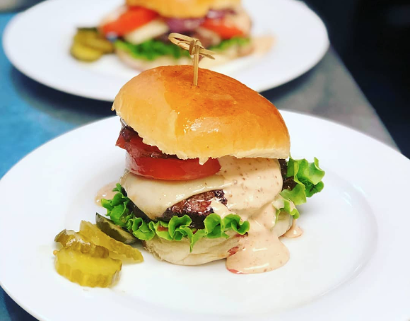 A duck-fat infused beef burger with caramelized onions and Raclette cheese on a brioche bun. - PHOTO VIA BITES & BUBBLES/INSTAGRAM