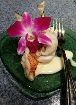 Butter-poached lobster tail over grains of paradise served with caramelized banana panna cotta and oyster root crisp