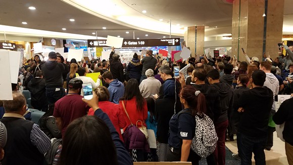 1:52 p.m.: The protest inside the airport's food court is about 200 feet away from where families and friends of the travelers affected are waiting. Many come over to watch up close. - DAVE PLOTKIN