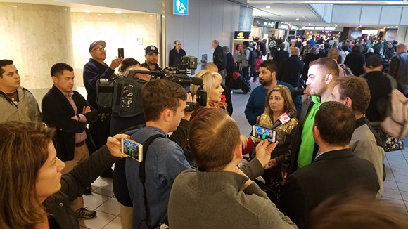 4:58 p.m.: Elias Habbabeh is interviewed for television with his parents, Syrians Abdulrazzak Habbabeh and Mary Safar. - DAVE PLOTKIN