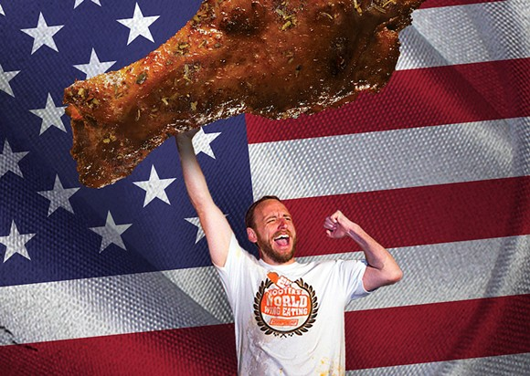 Champion competitive eater Joey Chestnut, hoisting a Photoshopped chicken wing - IMAGE COURTESY OF HOOTERS. THANKS A LOT.