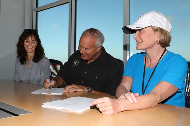 Monica Rivers, John Rivers and Lesa France Kennedy signing the contract to bring the newest 4 Rivers Smokehouse to One Daytona - COURTESY 4R RESTAURANT GROUP