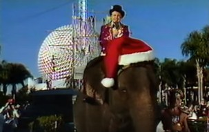 Regis Philbin riding a Santa hatted elephant past a circus in Epcot as part of the 1987 Walt Disney World Christmas Parade television special - IMAGE VIA PROGRESSCITYPUBLICTV | YOUTUBE