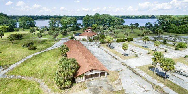 The current state of the former Lake Orlando Golf Club abandoned clubhouse. As seen immediately post-acquisition with Lake Orlando in the background. - IMAGE VIA LAKEORLANDO.COM