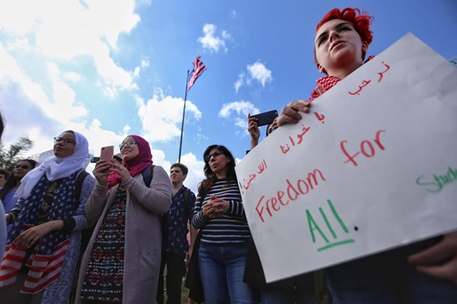 An officer from the student-run campus organization Students Organize for Syria holds a sign during a demonstration on UCF's Memory Mall protesting Trump's immigration orders. - PHOTO BY JOEY ROULETTE