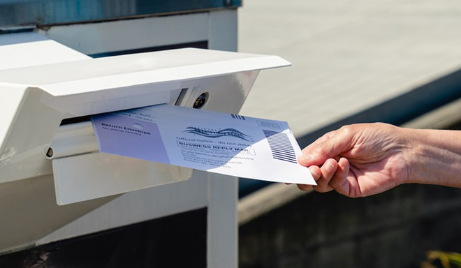 Putting a vote-by-mail ballot in the postbox. - ADOBE