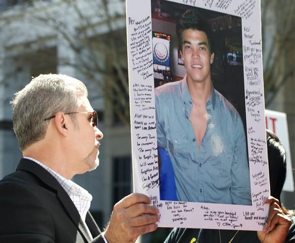 Rafael Zaldivar, left, holds a picture of his son. - PHOTO BY MONIVETTE CORDEIRO