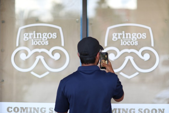 "A UCF student FaceTimes a friend to prove the imminent opening of Gringos Locos on campus. ""This is lit,"" the student exclaims. - PHOTO BY JOEY ROULETTE"