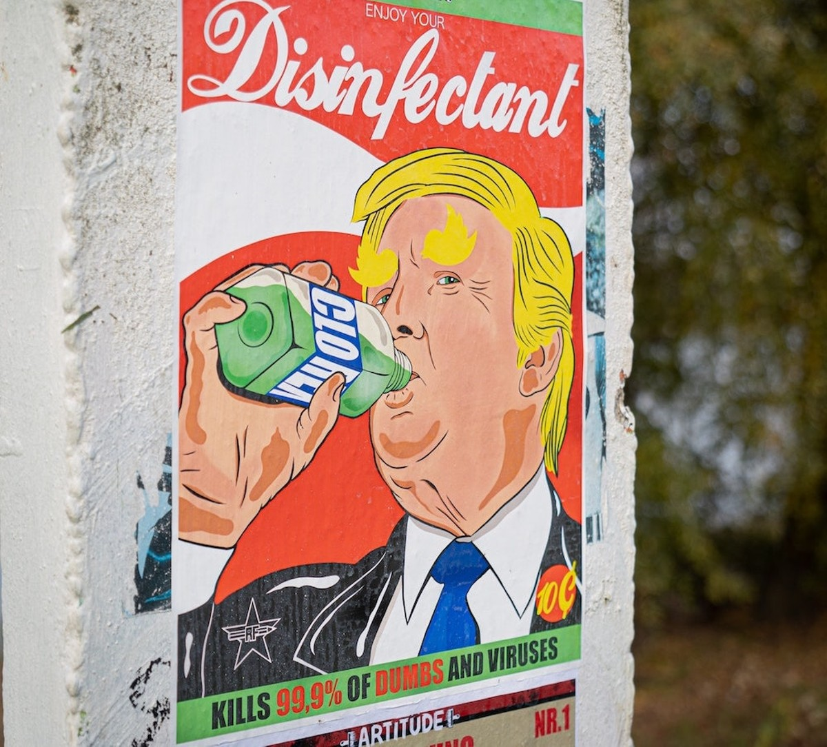 """Poster of an illustration showing Donald Trump drinking """"Clorex"""" with text """"Enjoy your Disinfectant — kills 99.9% of dumbs and viruses"""""""