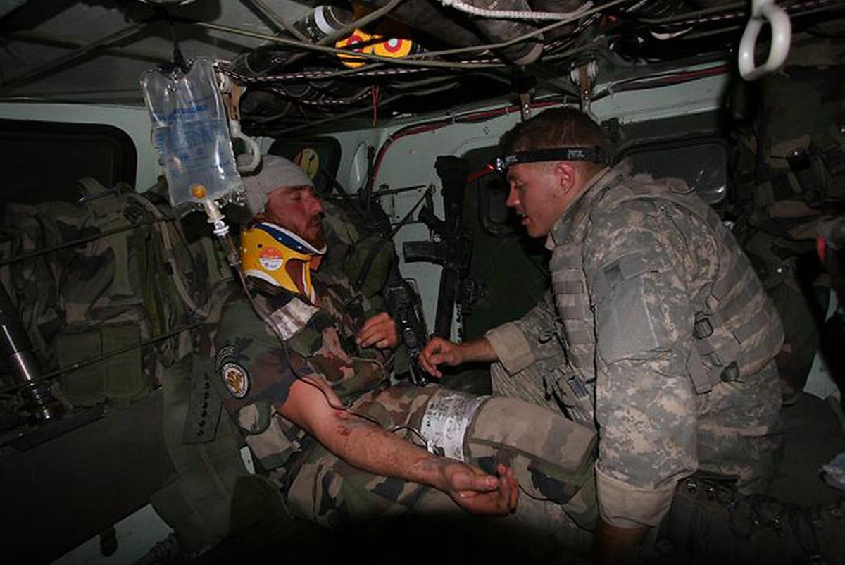 A U.S. Army Specialist treats a wounded French army soldier following an ambush in the Kapisa province of Afghanistan