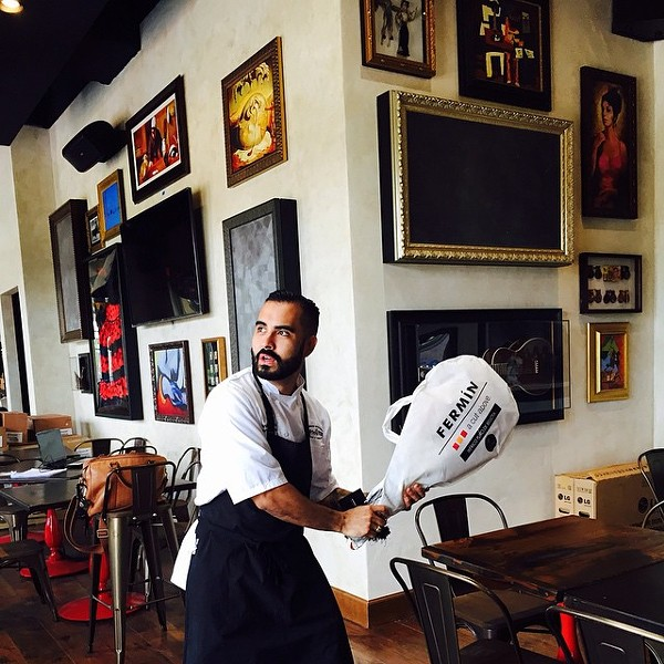 Tapa Toro's chef de cuisine making a jamón de bellota home run in anticipation of opening day - PHOTO VIA TAPA TORO ON FACEBOOK