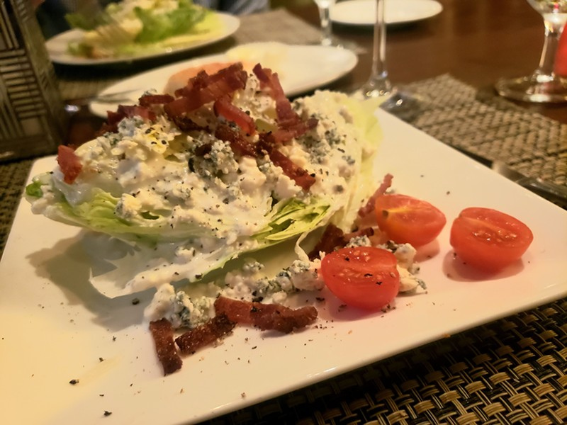 Classic wedge salad topped with bacon lardons and Danish blue cheese. - HOLLY V. KAPHERR